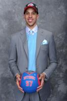 Austin Daye in a gray pinstripe suit holding a Pistons basketball.jpg