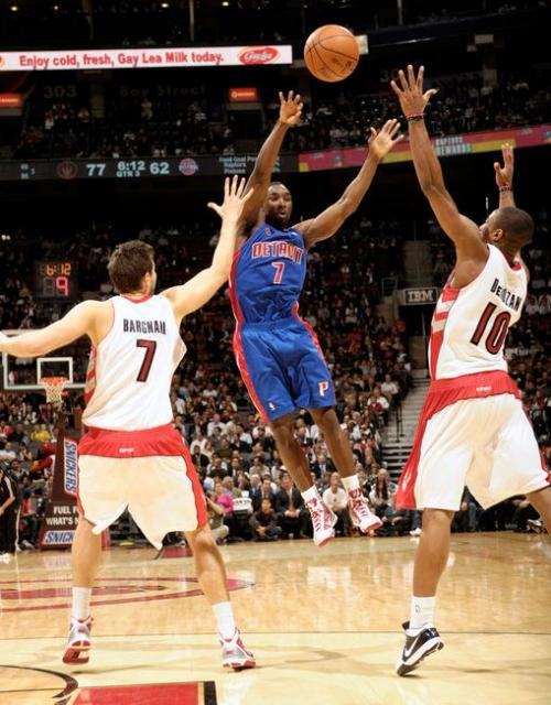 Ben Gordon tries to pass the ball over two Raptor defenders.JPG